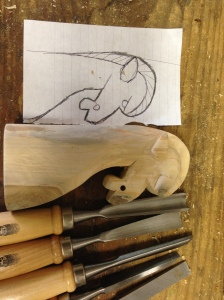 Carving the transferred design with an assortment of hand chisels